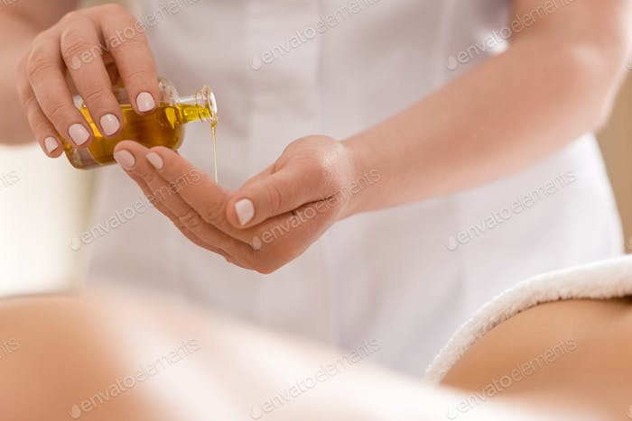 massage therapist using body oil for massage in spa salon