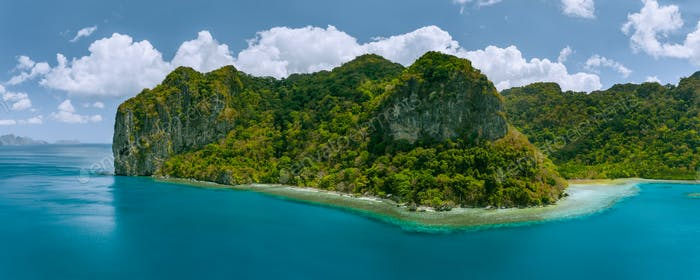 Aerial panoramic drone view of uninhabited tropical island with towering mountains and rainforest