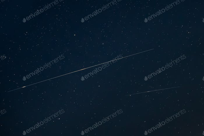 Two Meteoric Tracks In The Blue Night Starry Sky Background. Nat