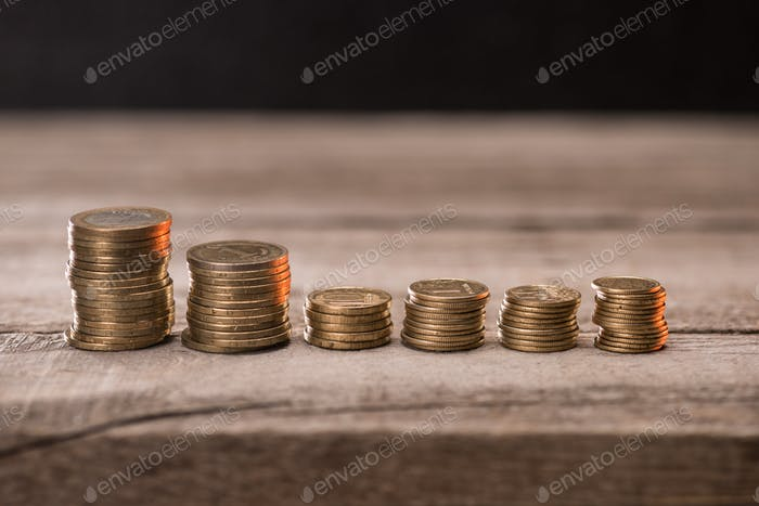 Stacks of coins on wooden tabletop, pile of coins concept