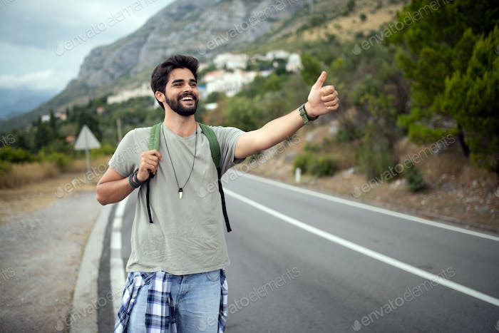 Hitchhiking young traveller man try to catch car on a forest road
