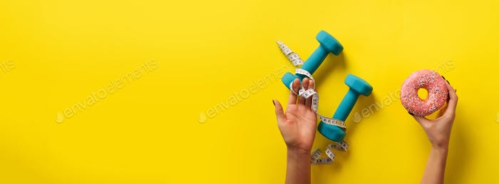 Female hand holding sweet donut, measuring tape, dumbbells over yellow background. Top view, flat