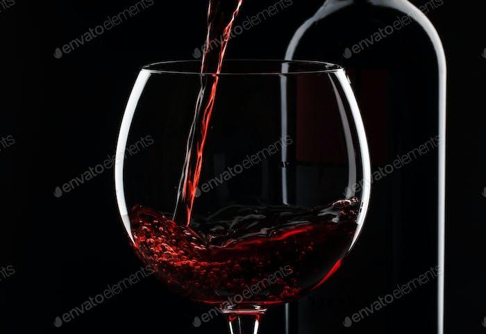 Rotwein in das Glas gießen