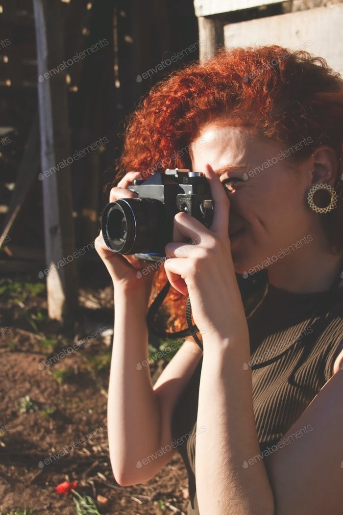 Young redhead photographer woman enjoying her passion outdoors