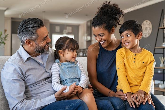 Glückliche ethnische Familie mit zwei Kindern auf der Couch