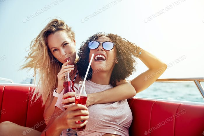 Laughing friends sitting on a boat enjoying drinks during vacation