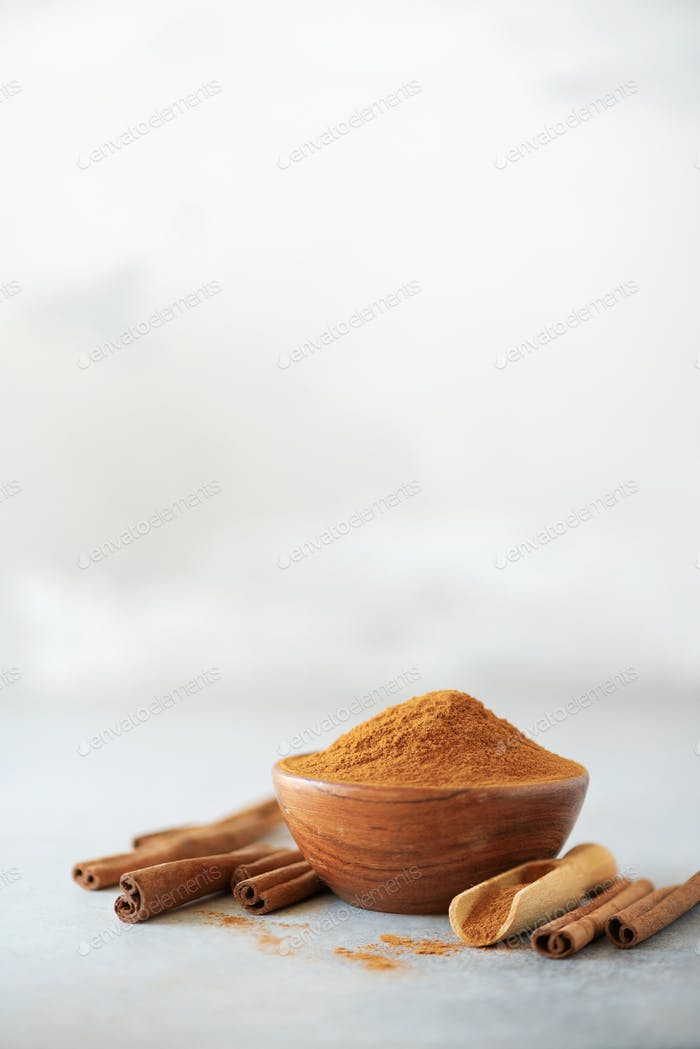 Cinnamon sticks and powder on grey background. Spices for ayurvedic treatment. Alternative medicine