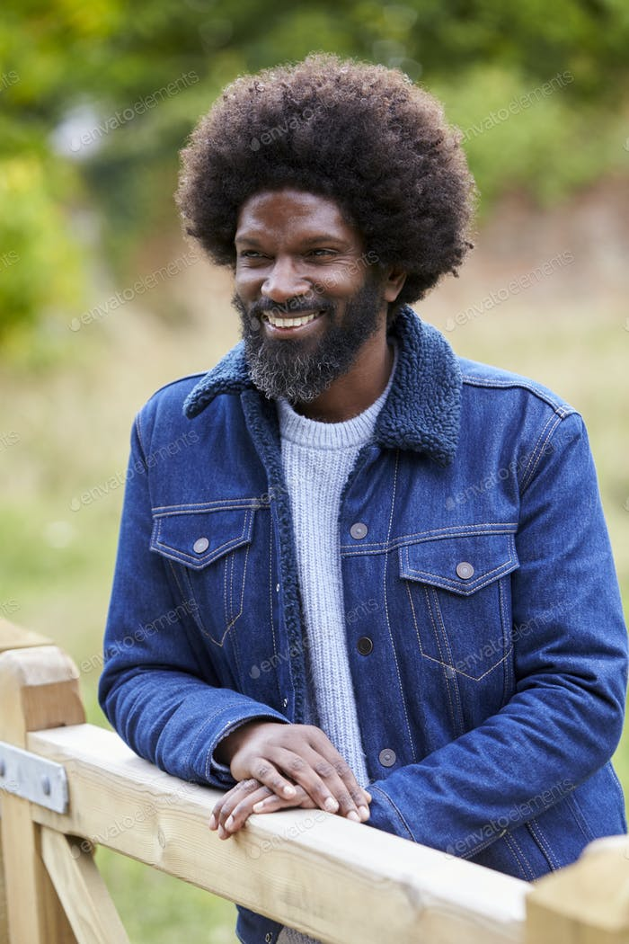 Happy adult black man leaning on a wooden fance in the countryside smiling, close up