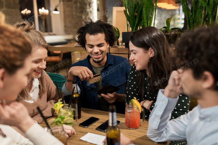 friends with drinks, credit card and bill at bar