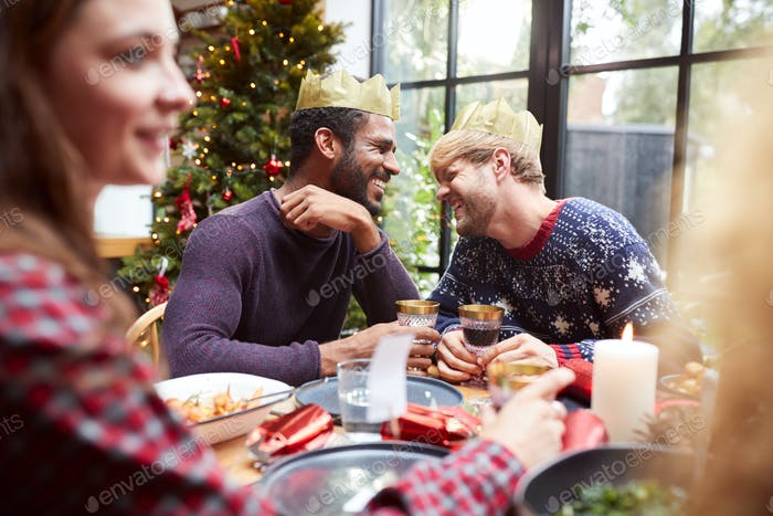 Gay Male Couple Sitting Around Table For Christmas Dinner Talking