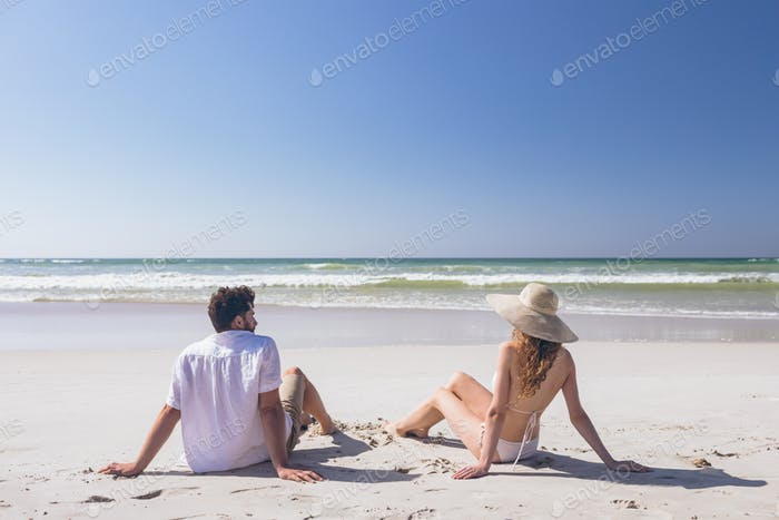 Rear view of young Caucasian couple relaxing sitting at beach on a sunny day.They are looking ocean