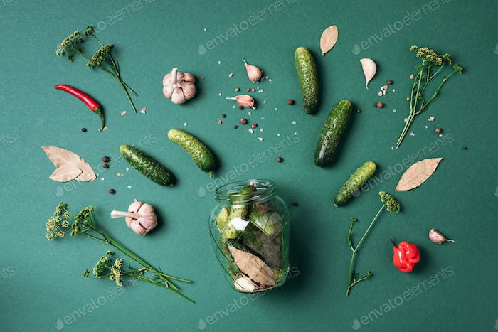 Ingredients for marinated gherkins, pickled cucumbers on blue background. Culinary recipe. Concept
