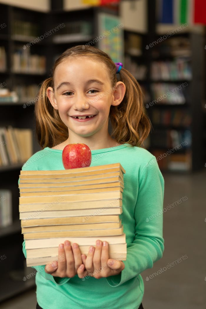 Smiling Caucasian schoolgirl with books and apple standing in library at elementary school