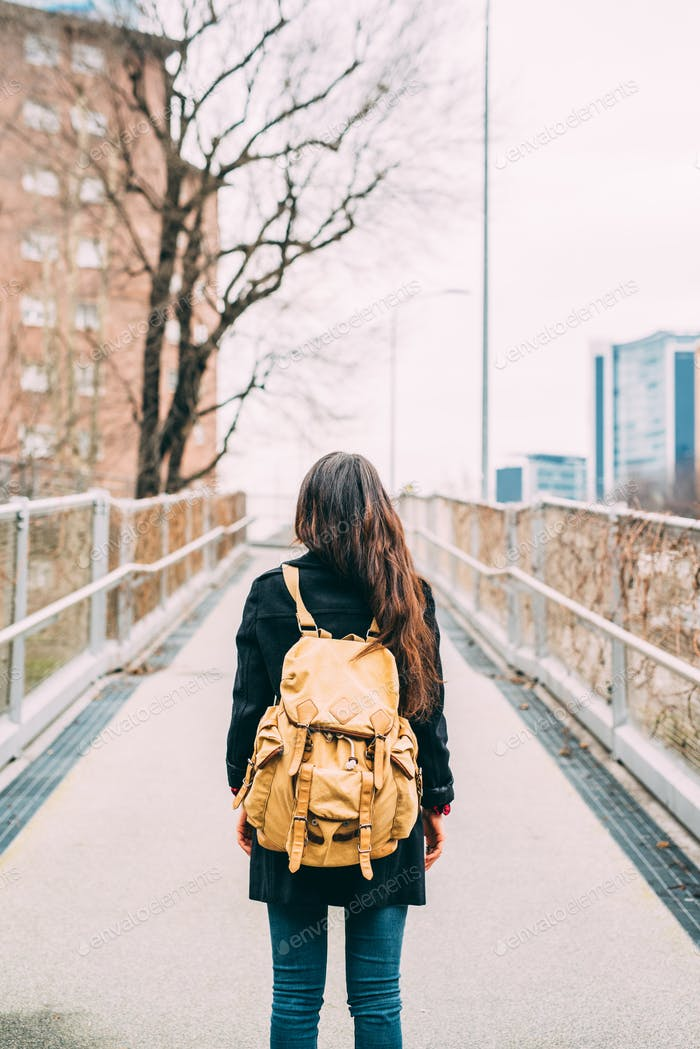 Rear view of young woman wearing backpack walking outdoor in the