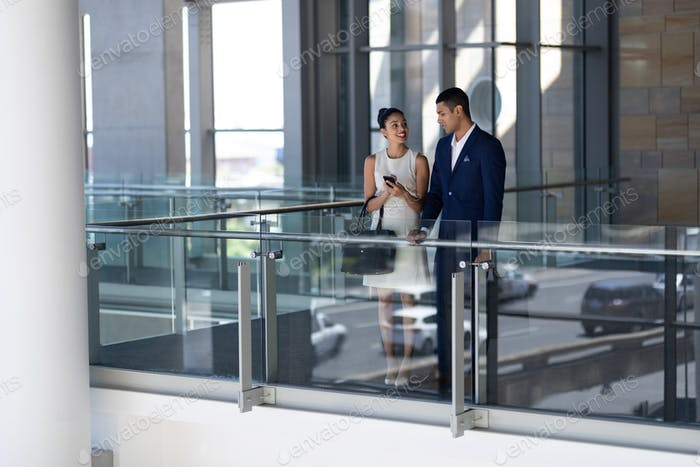 Elegant young business people interacting with each other standing in modern office