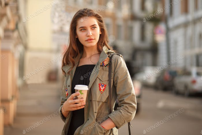 youth pretty female with coffee on street