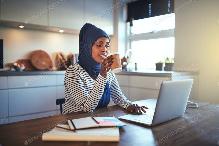 Young Arabic entrepreneur drinking coffee while working in her kitchen
