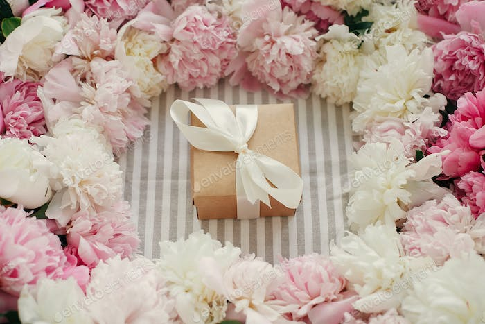 Craft gift box and peonies bouquet on rustic table cloth