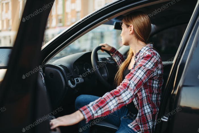 Female driver beginner sitting in a car