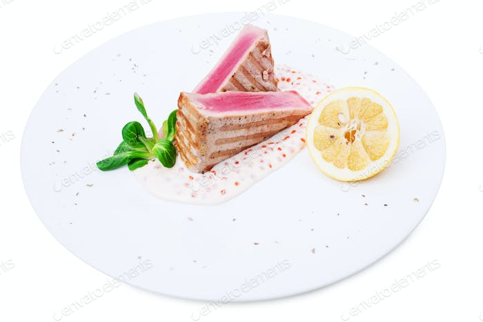 Grilled tuna fillet with sauce and lemon.