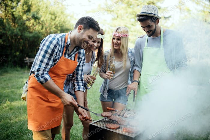 Group of friends making a barbecue together outdoors in the nature