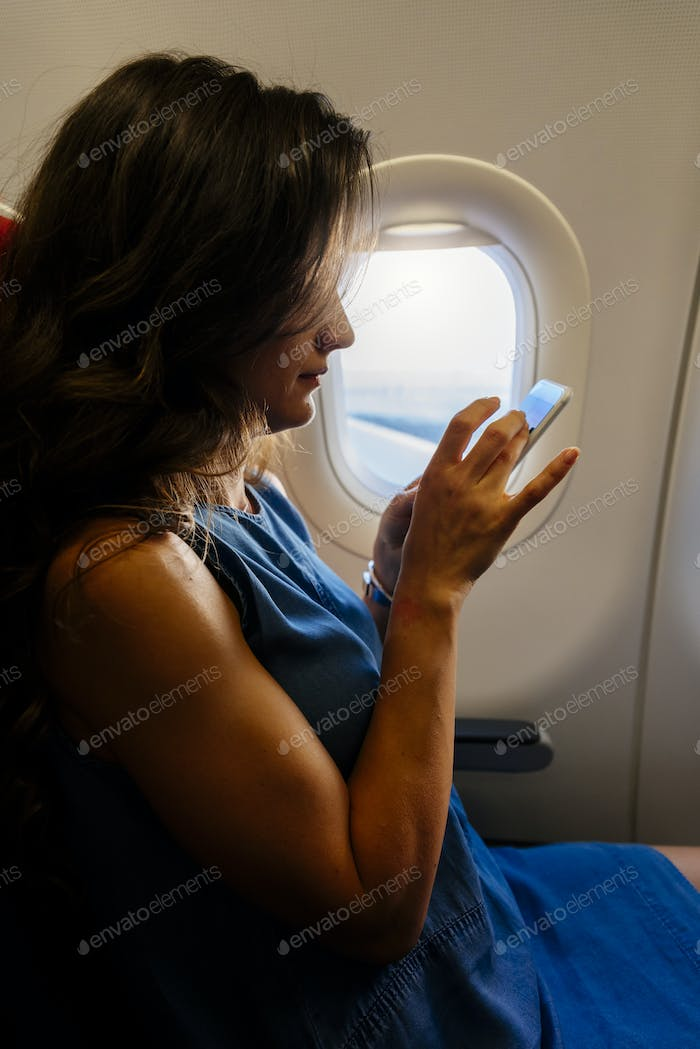 Young pretty business woman using mobile into the plane.