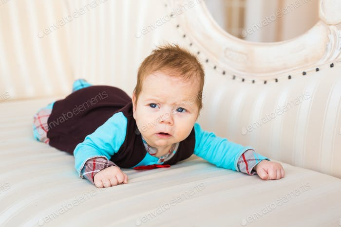 Close-up portrait of baby boy with red hair and blue eyes. Newborn child lyling in couch.
