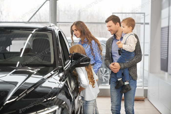 Children with parents looking at auto salon through window