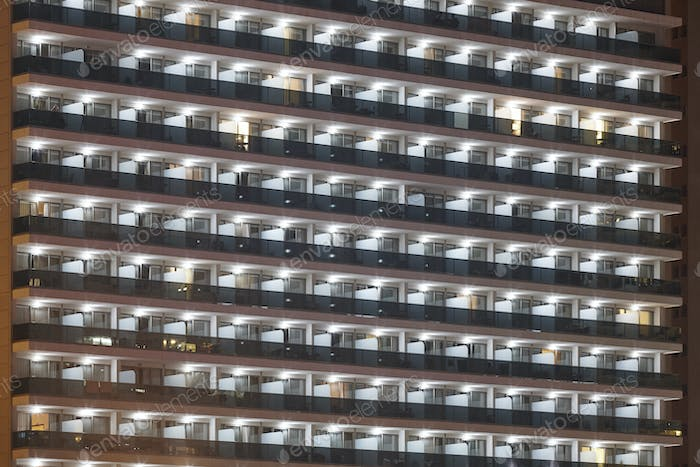 Hotel balconies facade by night. Tourism apartments. Residential. Horizontal