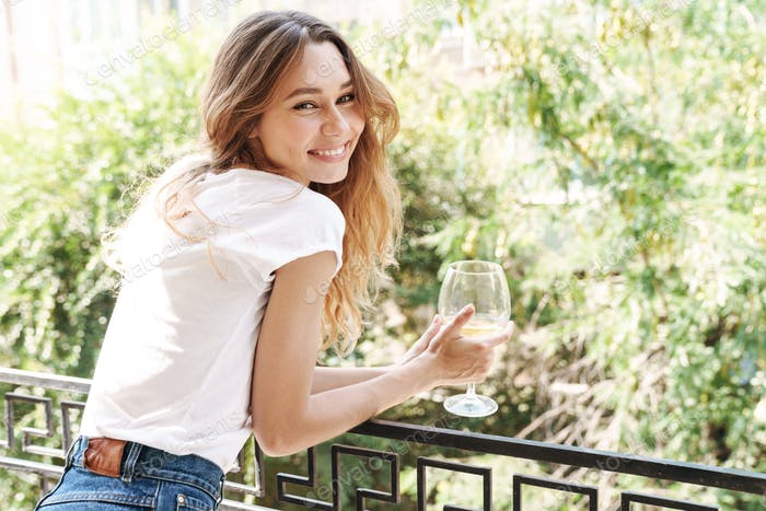 Image of lovely young woman smiling and drinking wine outdoors