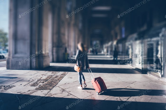 Tilt shift photo of a young girl with red luggage exit from Mila