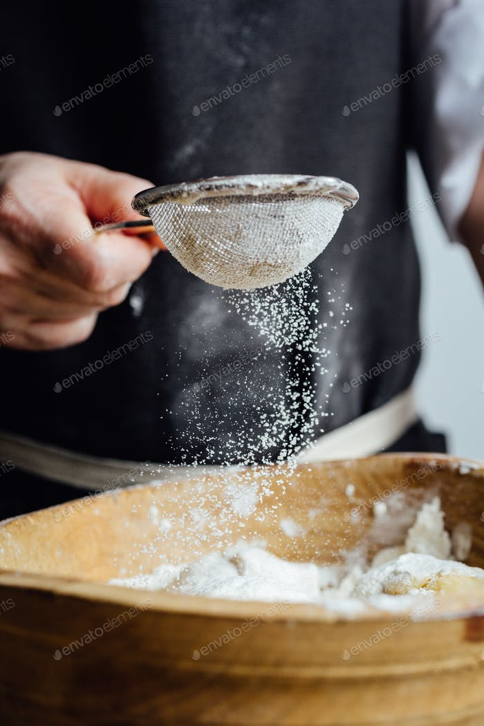 Person, die Gebäck mit Mehl bedeckt