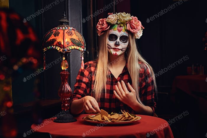 Young blonde girl with undead makeup in flower wreath eating nachos at a mexican restaurant.