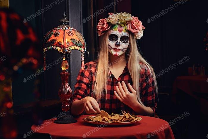 Молодая блондинка с макияжем нежити в цветочном венке ест начос в мексиканском ресторане.