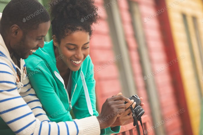 Front view of happy African American couple using digital camera while standing at beach hut