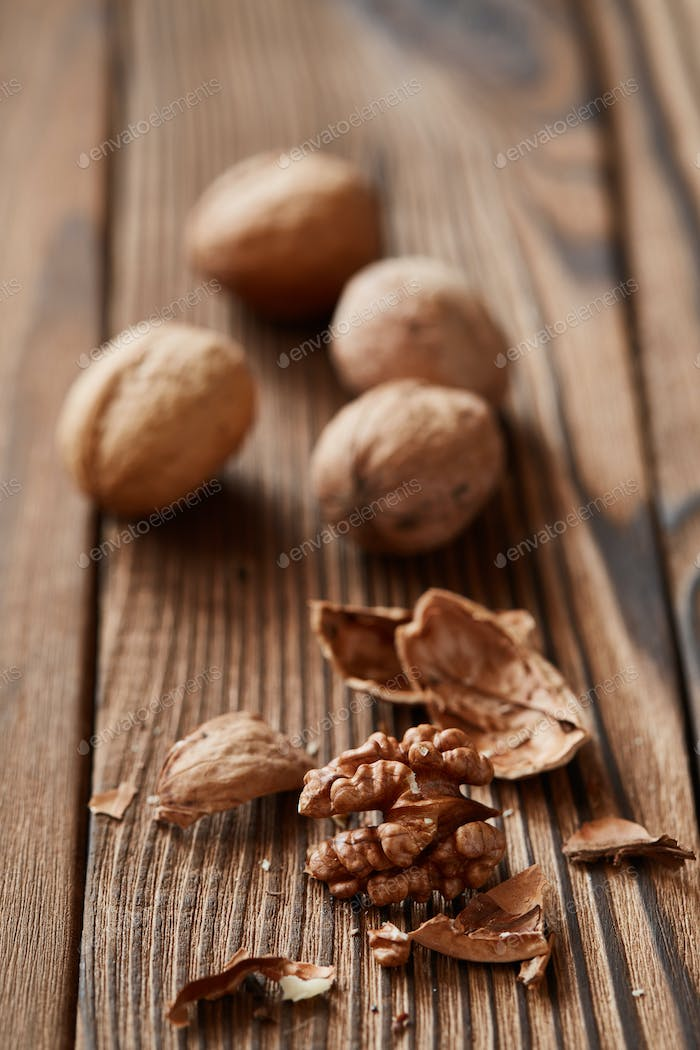 Walnuts and kernels on a dark rusty wood backdrop
