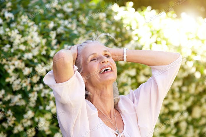 carefree older woman with hands in hair