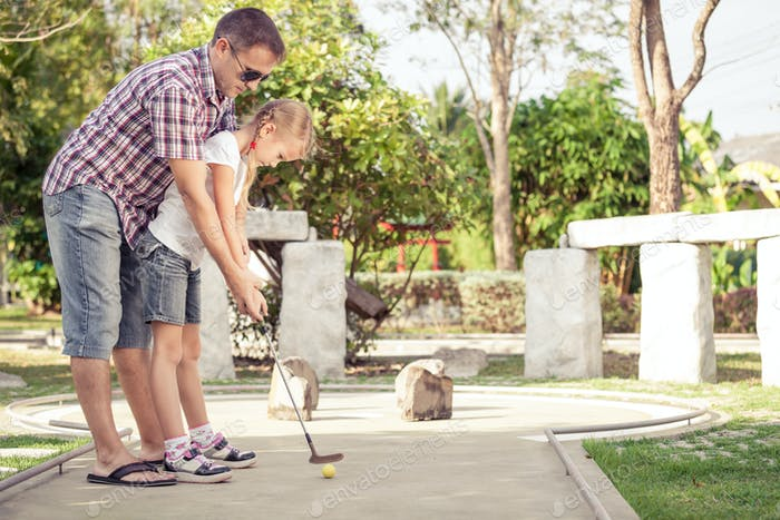 Cheerful young man teaching his daughter to play mini golf at th