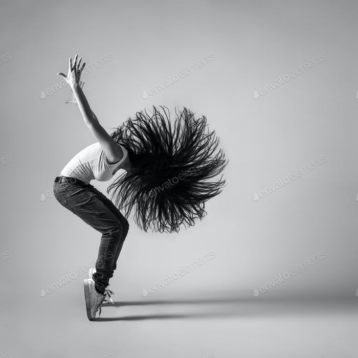 beautiful dancer girl squatting with flying hair