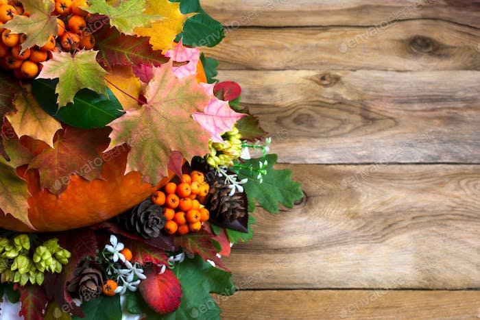 Thanksgiving greeting with  maple leaves on old wooden table