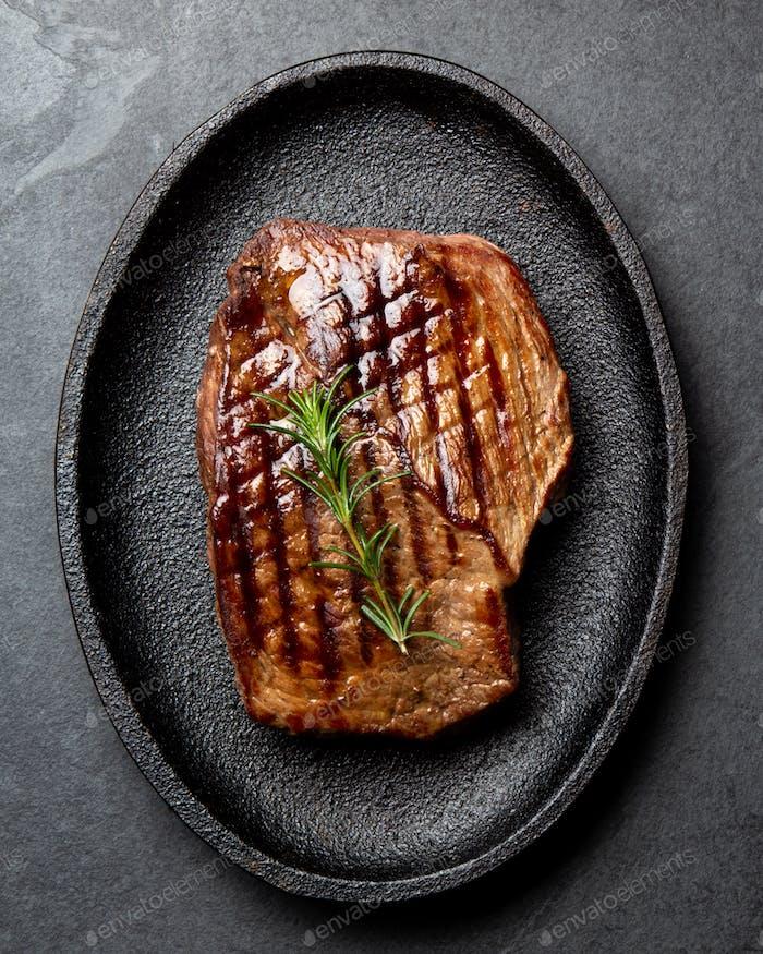 Gegrilltes Rindfleischsteaks mit Gewürzen auf schwarzem Teller.