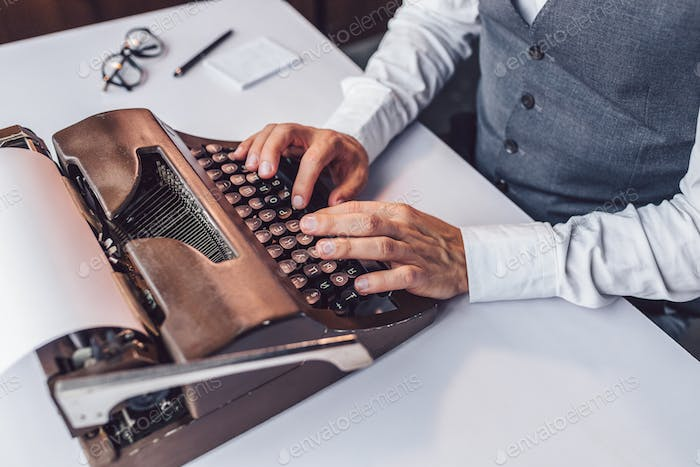 Male hands typing on a retro typewriter