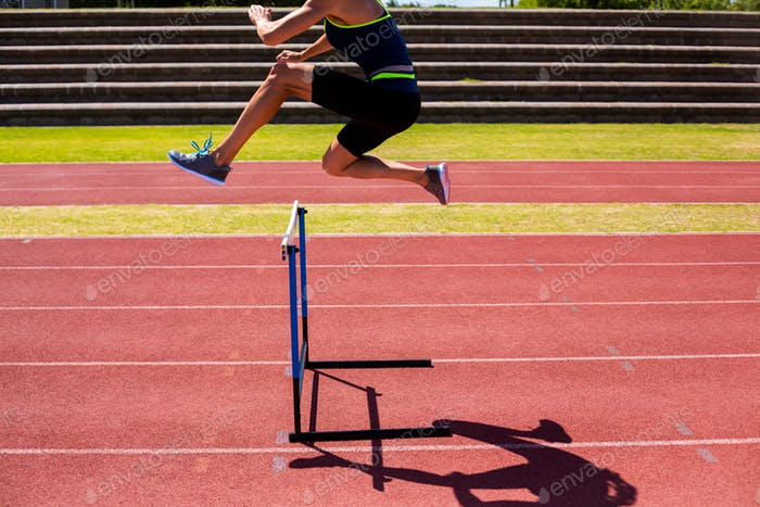 Female athlete jumping above the hurdle
