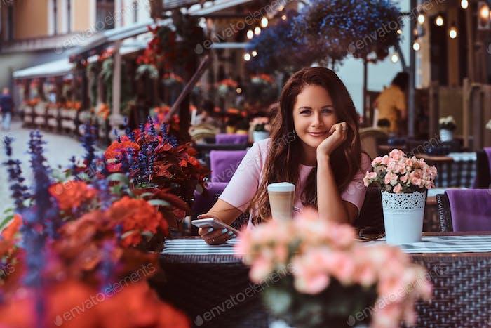 Porträt einer Geschäftsfrau mittleren Alters, die in einem Café im Freien sitzt.
