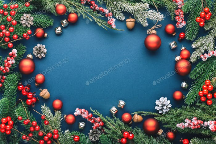 Christmas Frame with Red Decorations an Evergreen Branches on Dark Blue Background.