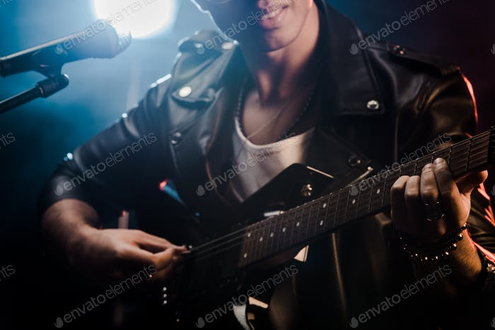 partial view of male musician singing in microphone and playing on electric guitar on stage during