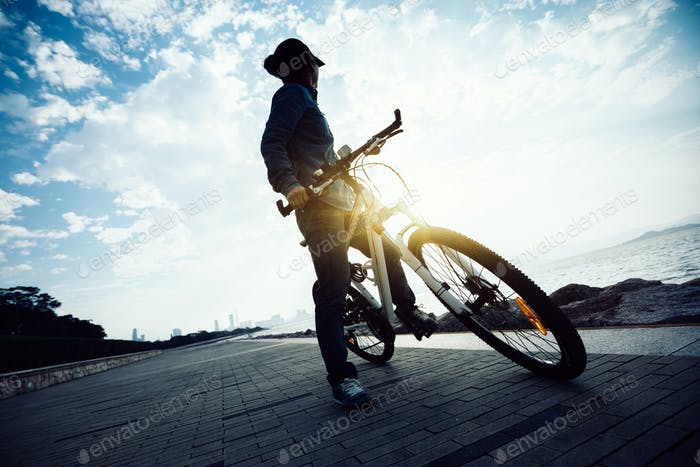 Cyclist looking the sunrise landscape