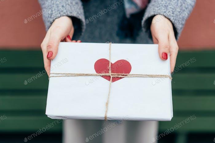 Draufsicht eines Geschenks in Papierverpackung mit einem Herzen in weiblichen Händen außen dekoriert