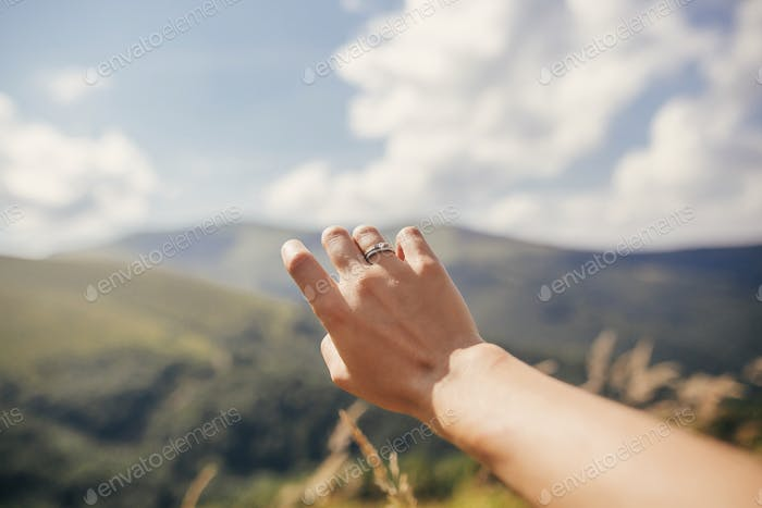 Traveler hand reaching out to mountains with engagement ring