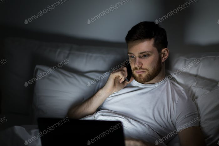 man with laptop calling on smartphone at night